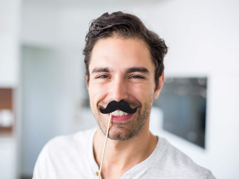 Man wearing fake moustache for Movember