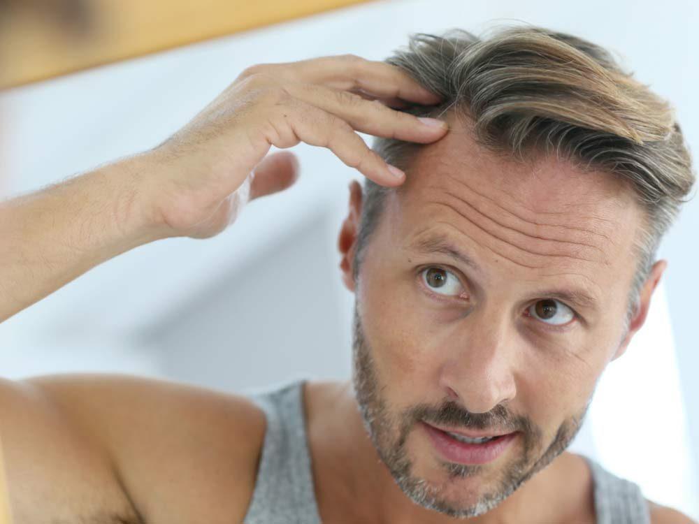 Man spotting hair loss in mirror