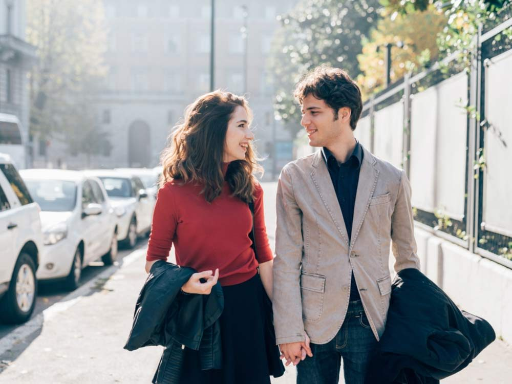 Couple holding hands while walking on street
