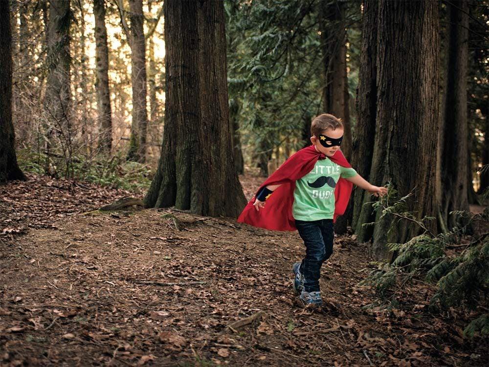 Boy crashing through leaves in forest