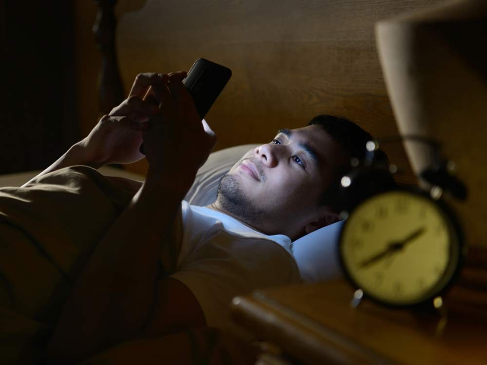 Man browsing through smartphone in bed at night
