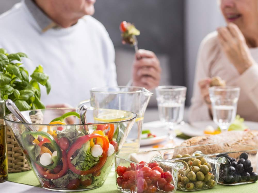 Elderly couple eating healthy salad meal