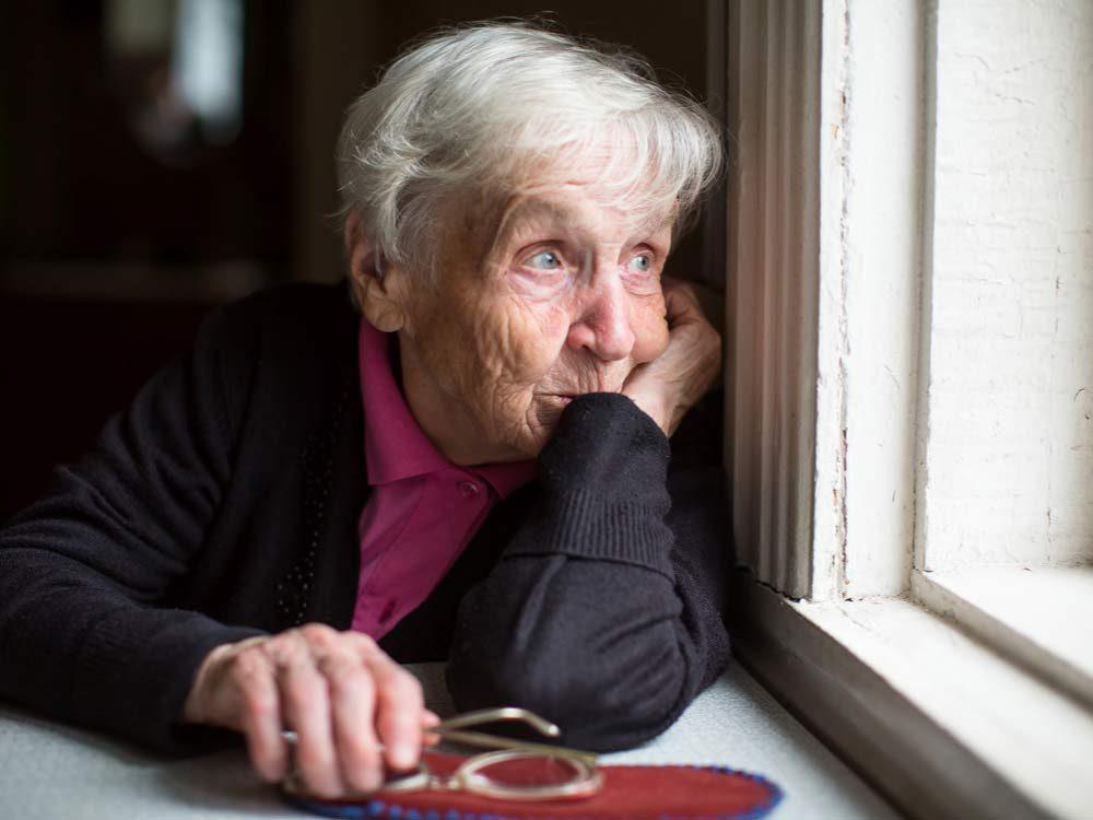 Elderly woman looking out of window