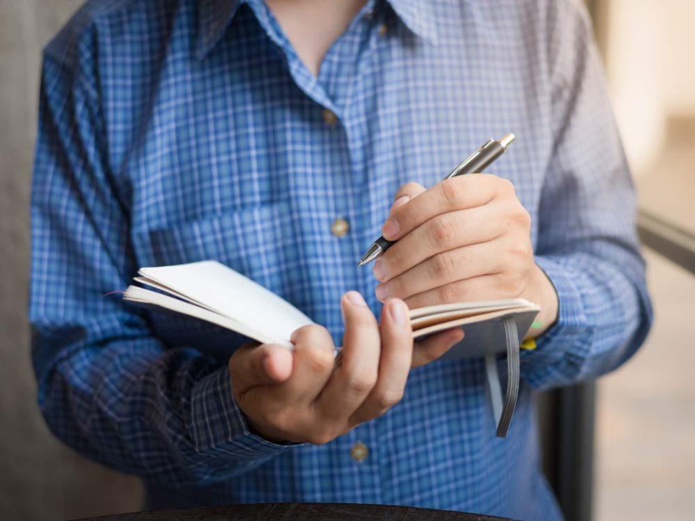 Left-handed man writing