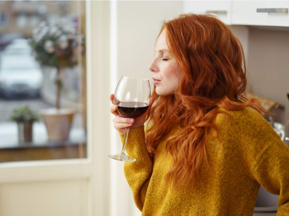 Red haired woman drinking wine
