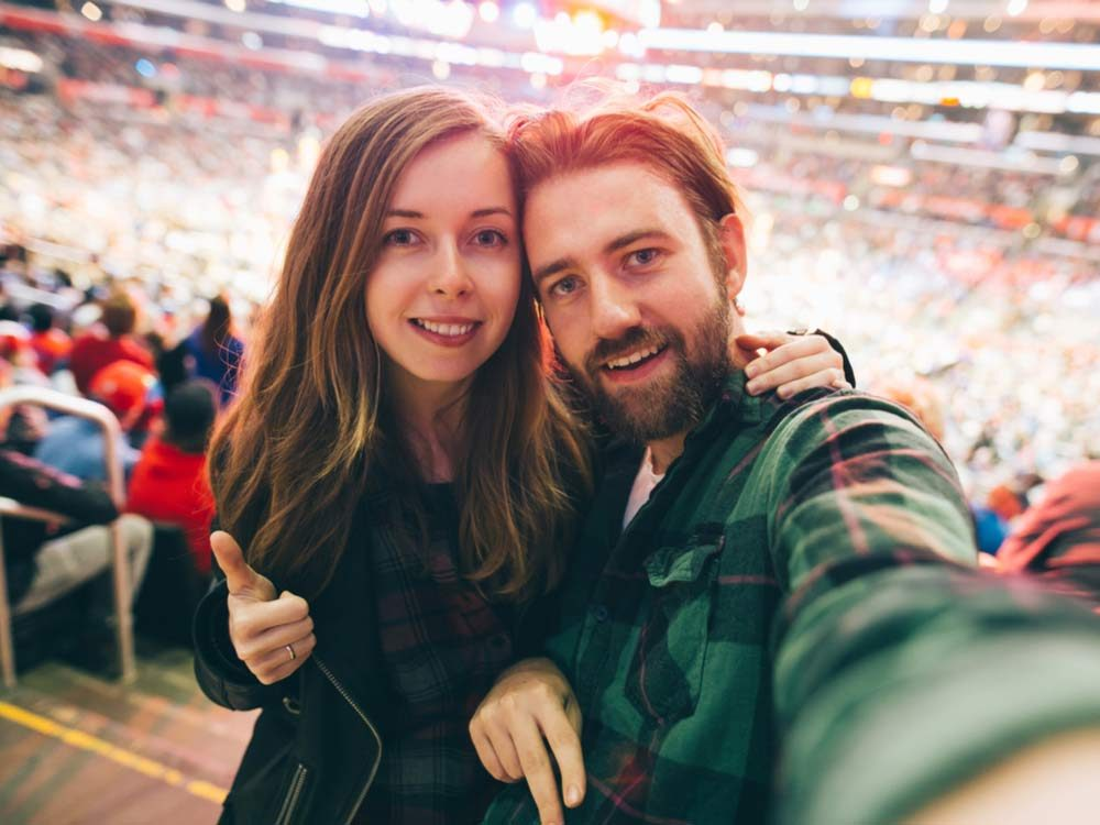 Couple taking selfie at sporting event