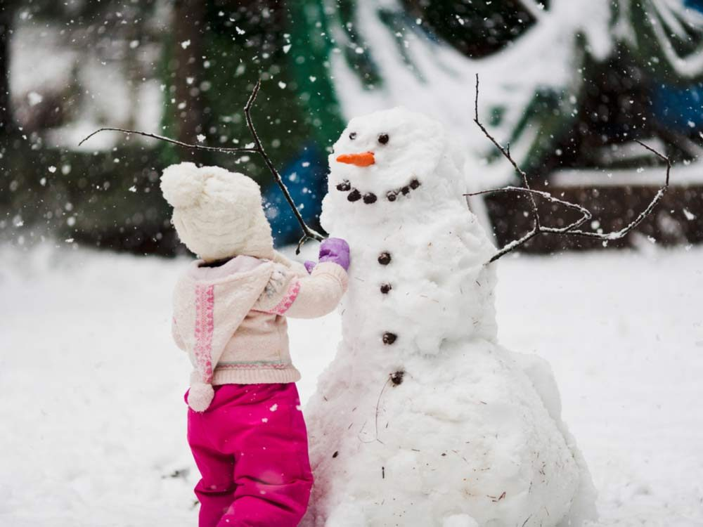 Young girl building snowman