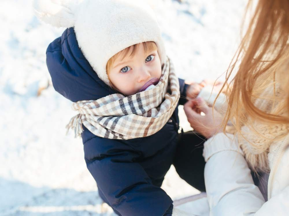 Mother bundling up her young daughter for winter