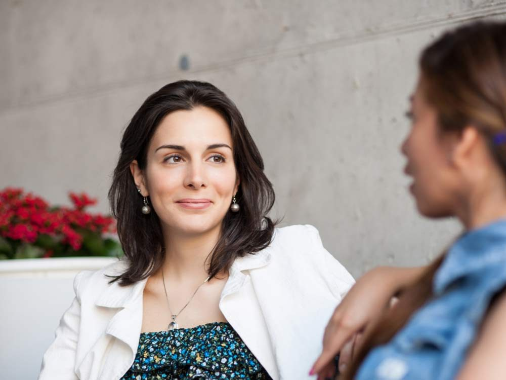 Woman examining facial features of friend