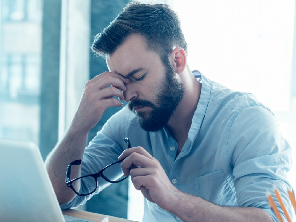 Man suffering from lack of sleep at work