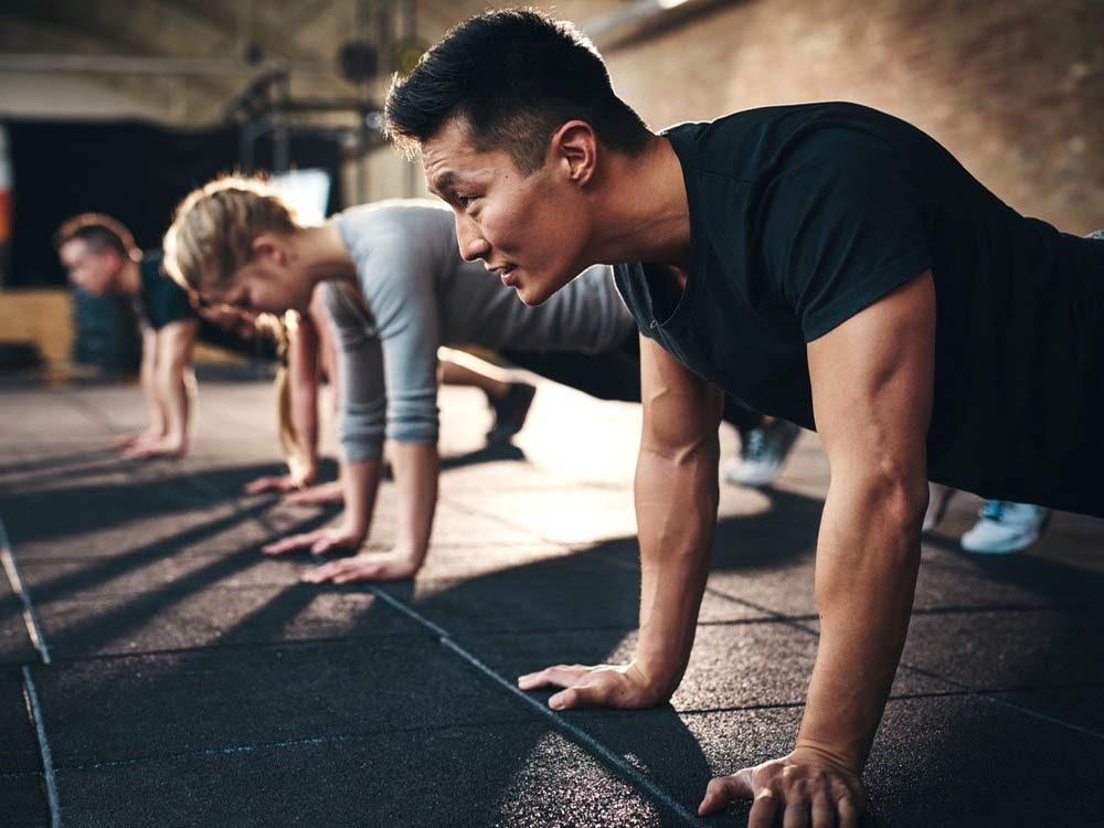 Three men planking in gym