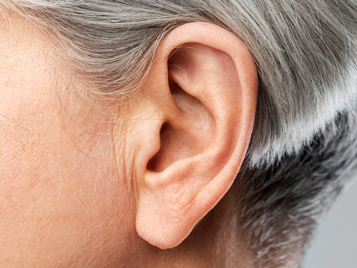 Body parts - hearing, body part and old age concept - close up of senior woman ear