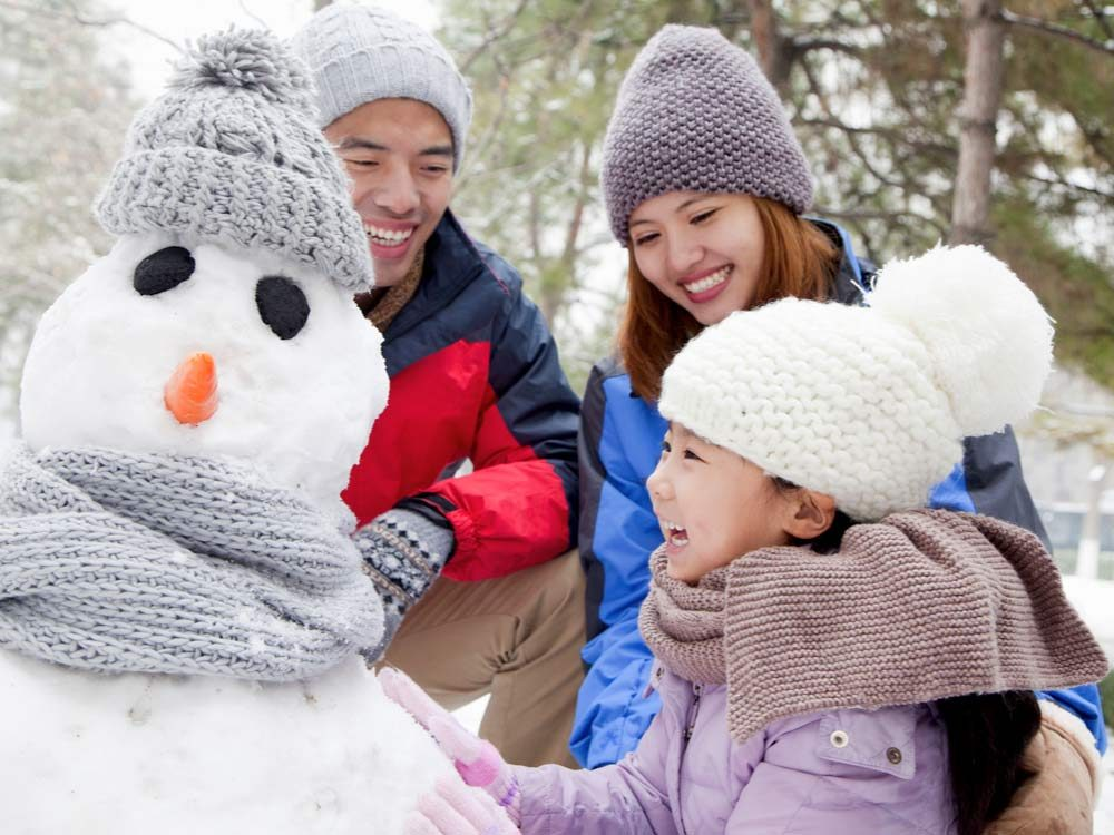 Chinese family building snowman