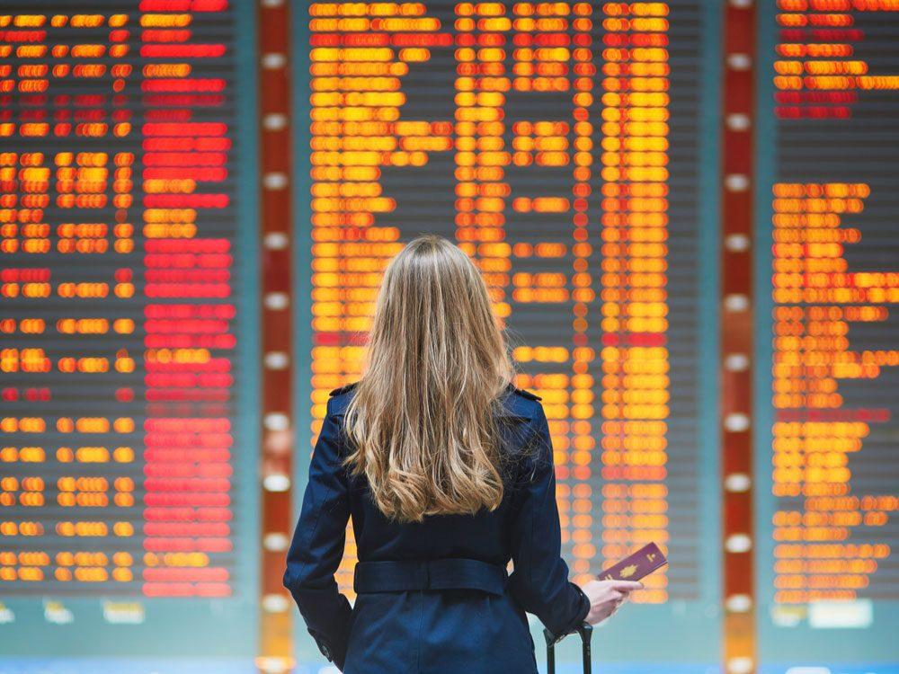 Woman looking at flight information board at airport