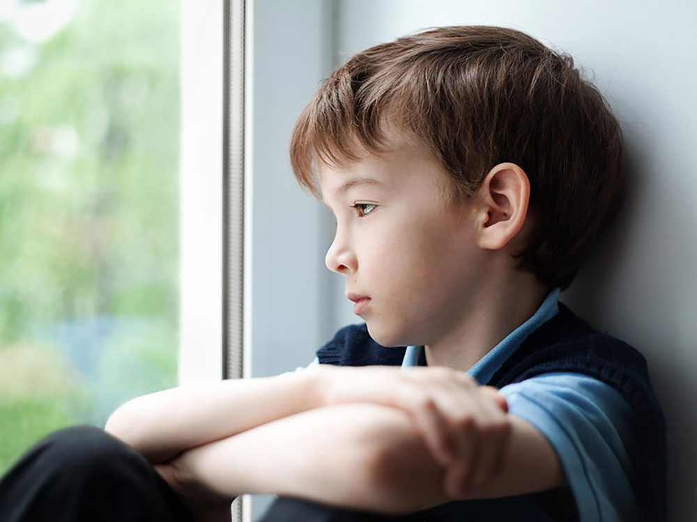 Lonely boy looking out of window
