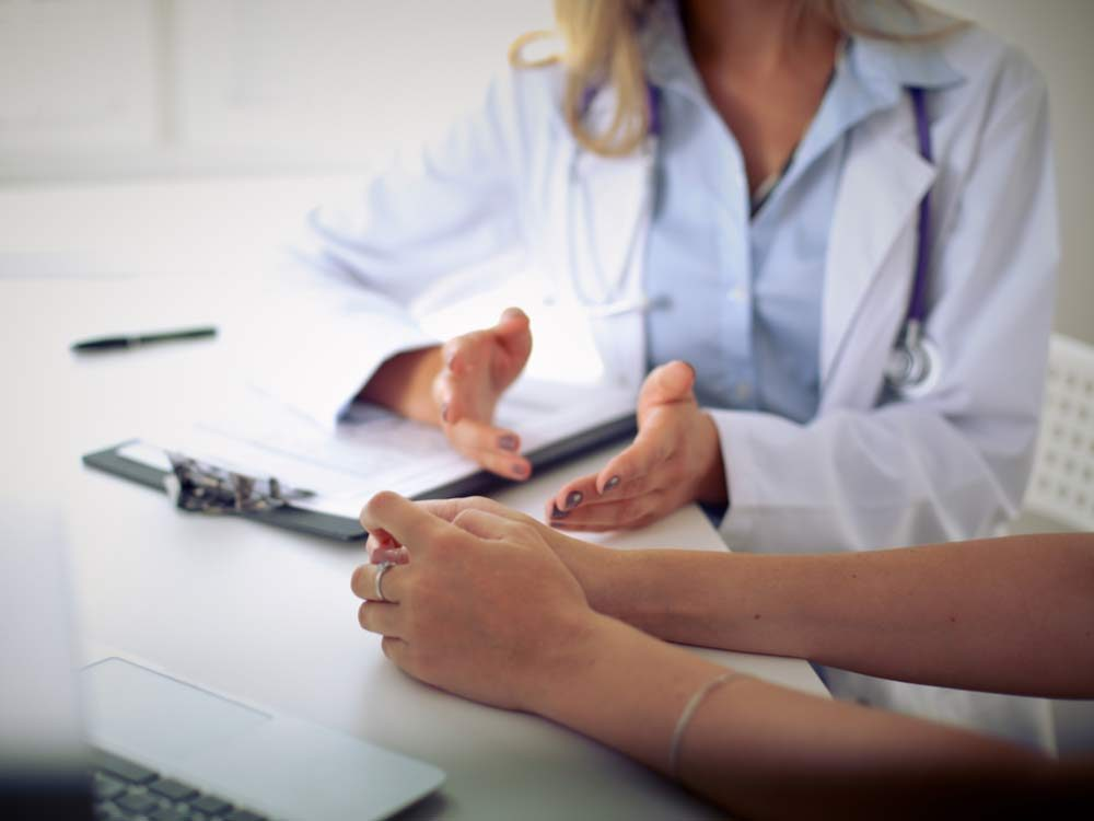 Hands of doctor speaking with patient