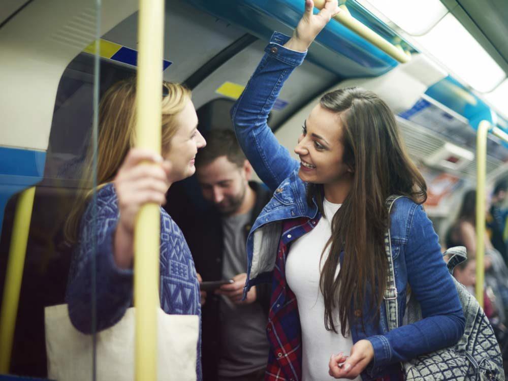 Friends talking in subway train