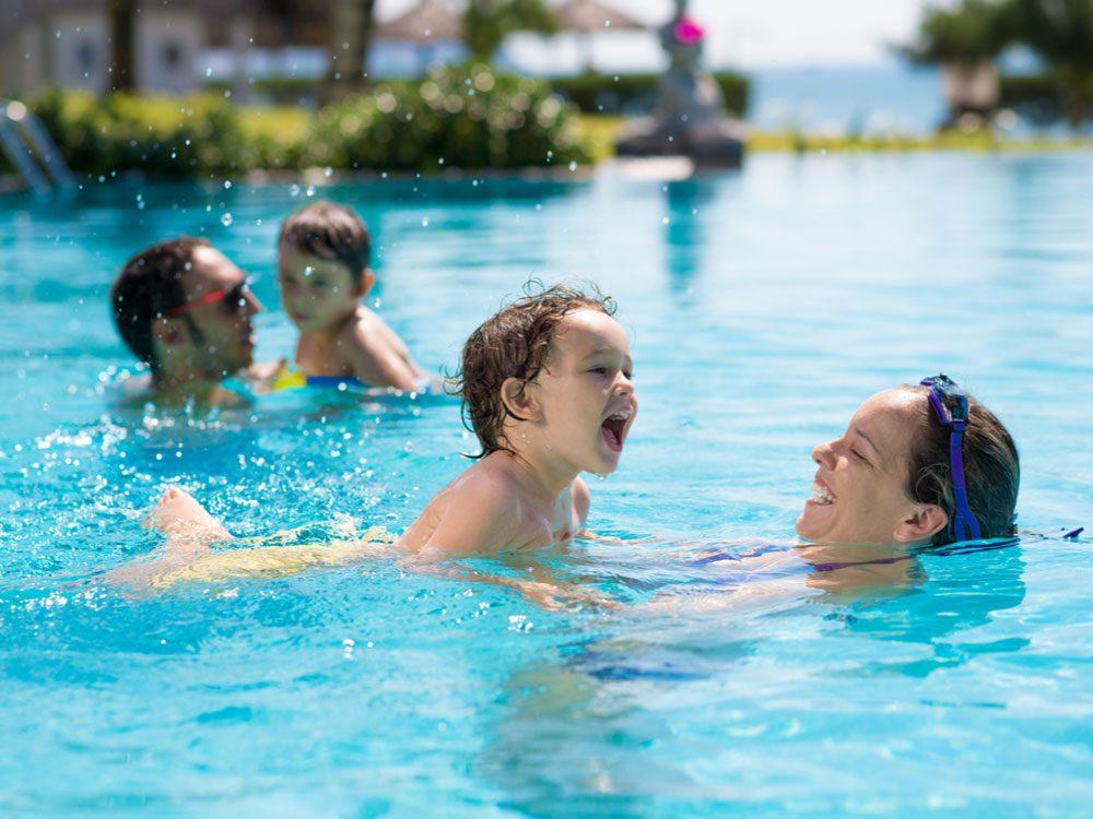 Happy family swimming in public pool