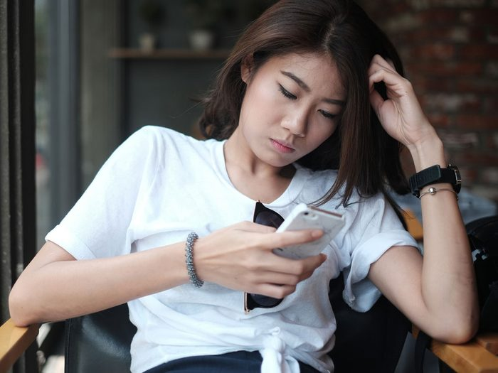 Sad woman checking social media on her smartphone