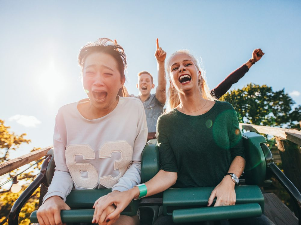Two female friends riding a rollercoaster