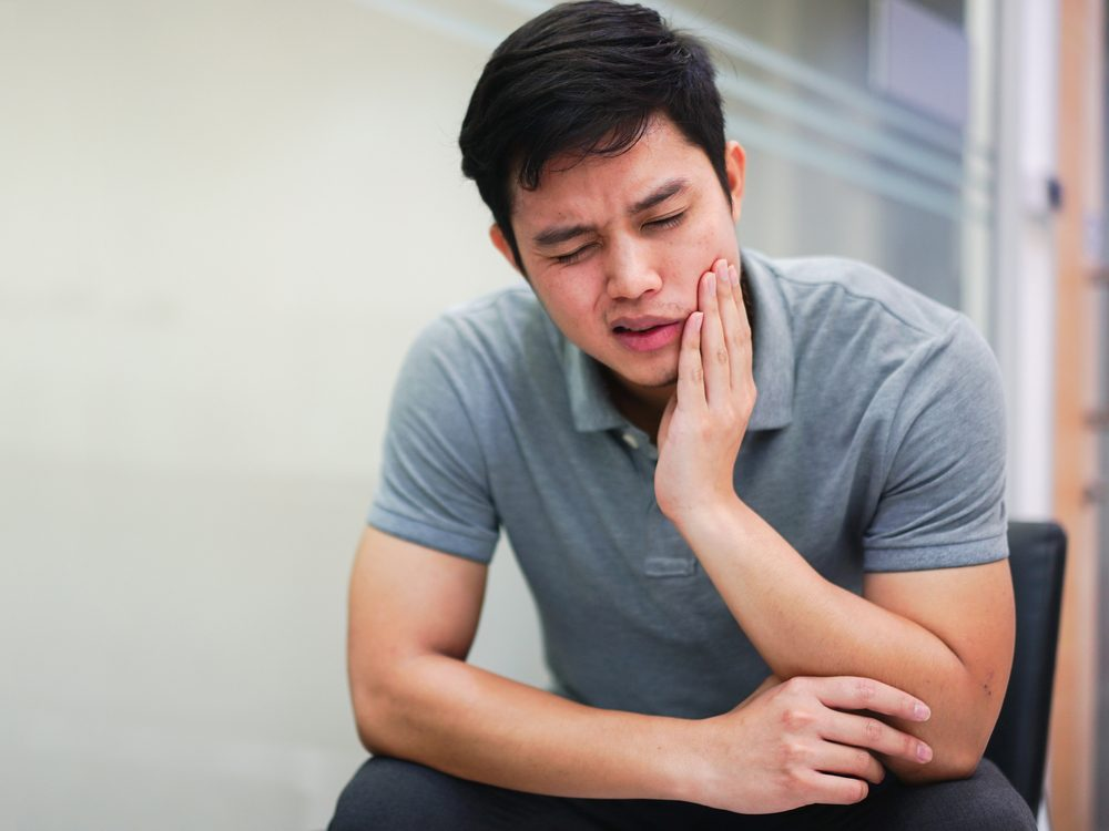Asian man experiencing pain from wisdom teeth