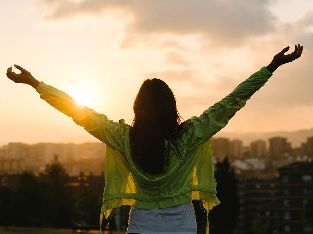 Woman celebrating at sunrise while overlooking city skyline