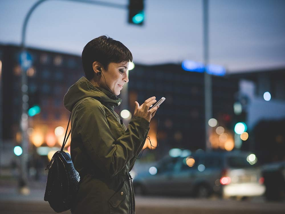Woman texting on her smartphone while waiting to cross the street at night