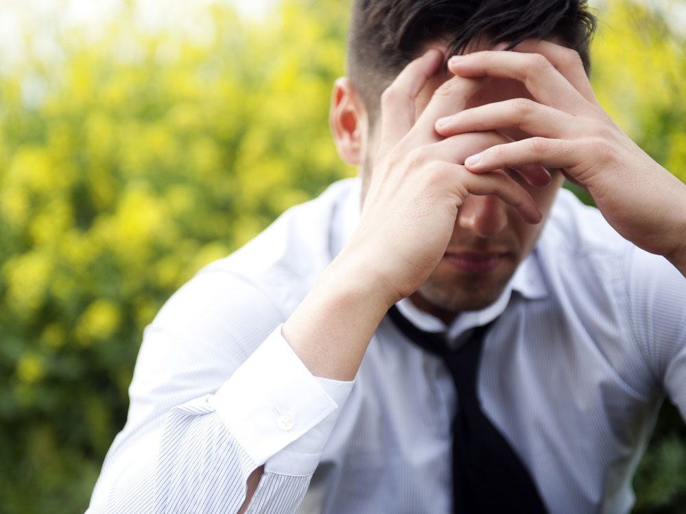 Stressed businessman with hands over his face