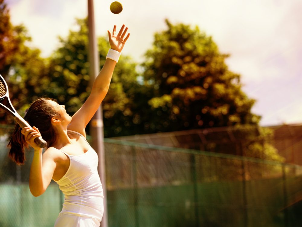 Woman playing tennis and throwing tennis ball
