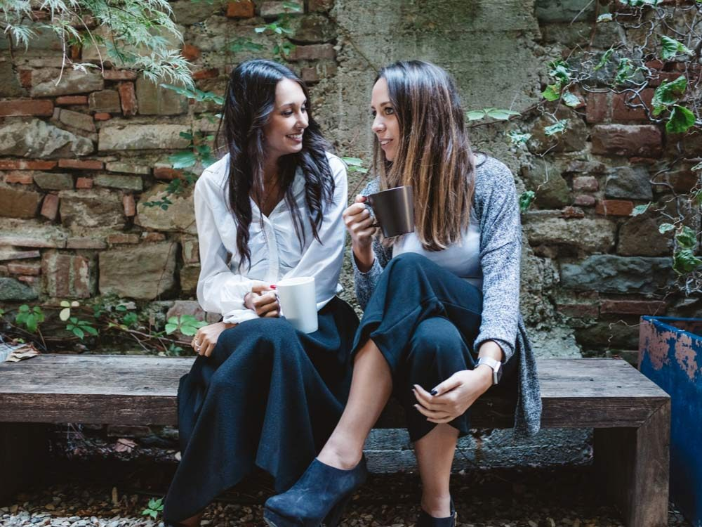 Two female friends talking in courtyard while drinking coffee