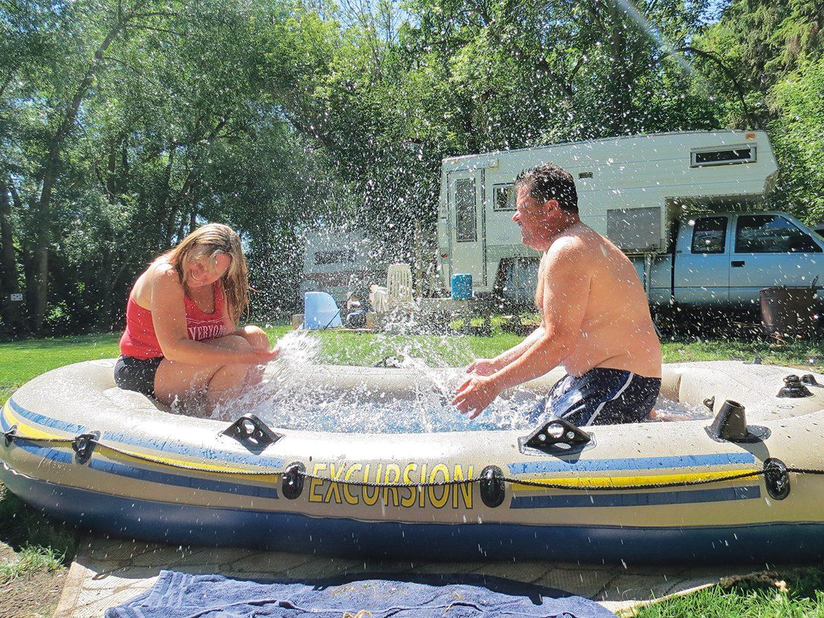 Making a splash water photography - couple splashing in dinghy