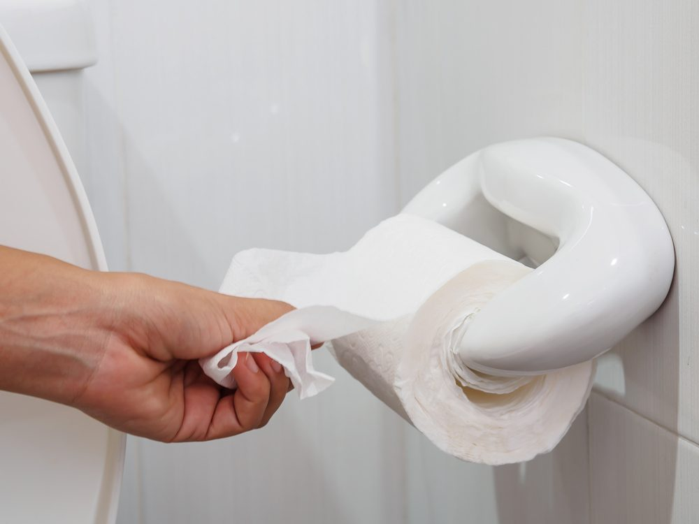 Hand grabbing sheet of toilet paper on toilet paper roll