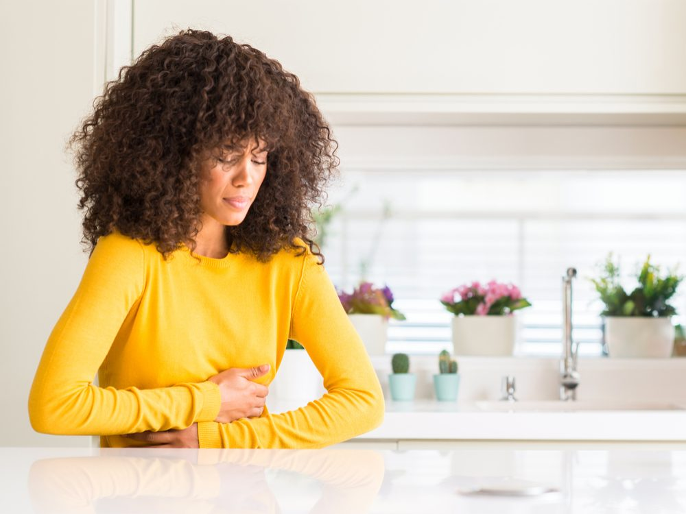 Woman clothing stomach in pain at kitchen table in yellow shirt, upset stomach
