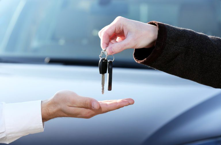 Car keys being handed to person