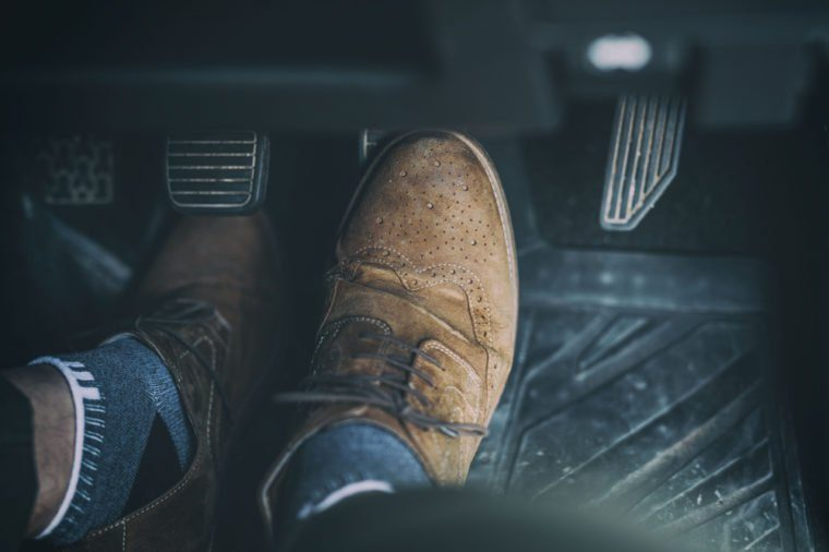 Man's foot on car pedal