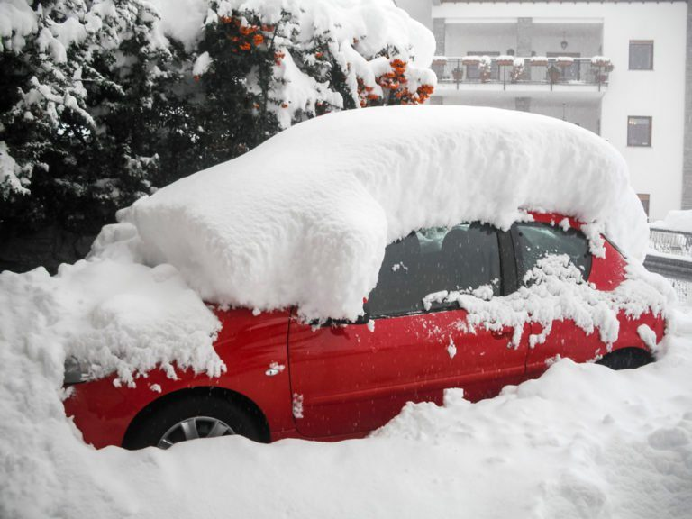 Red car buried in snow