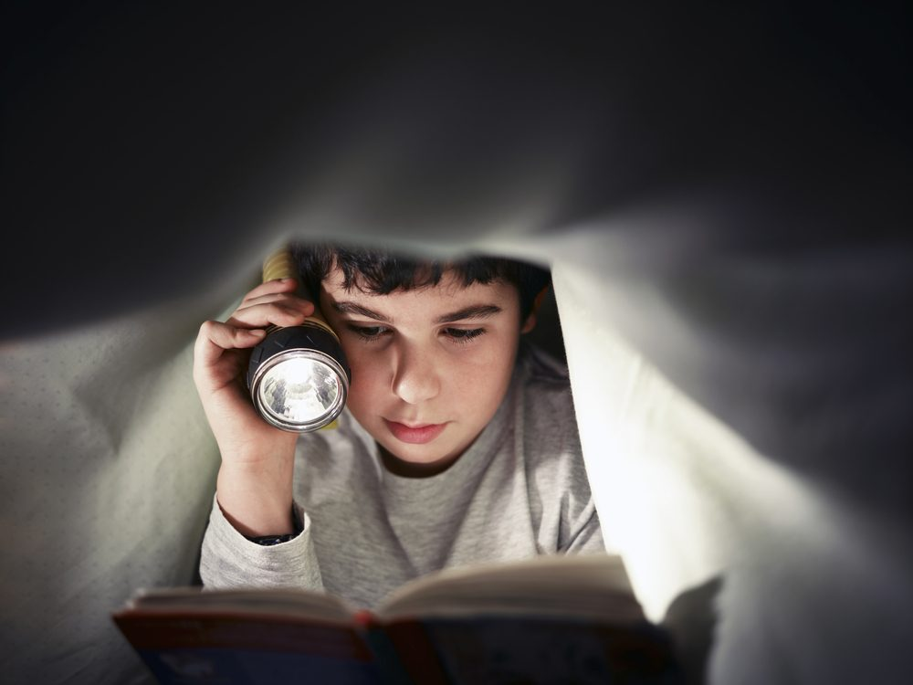 Reading under blankets at night