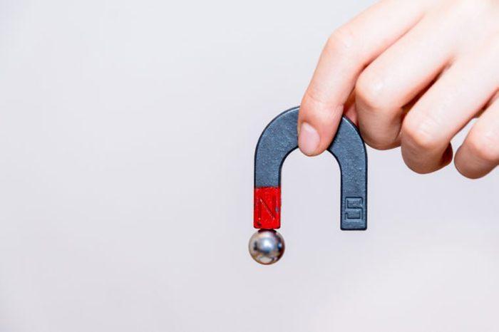 Close up of male hand holding horseshoe magnet