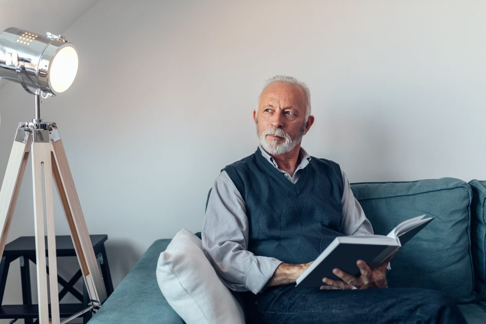 Old man reading in his living room