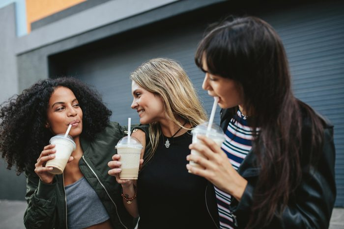 Female friends drinking smoothies outside