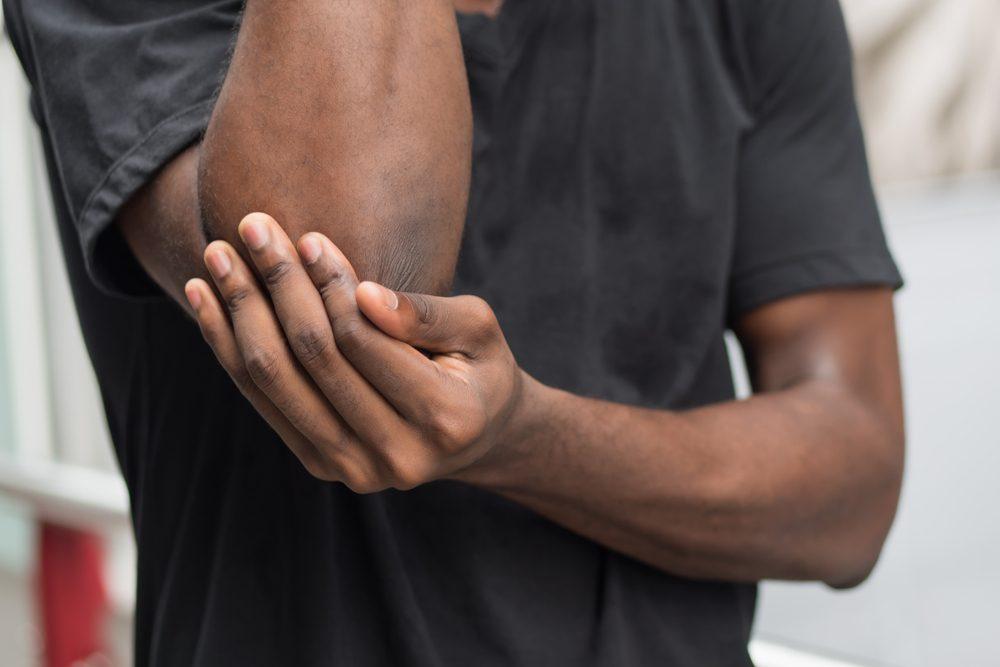 Man rubbing his elbows