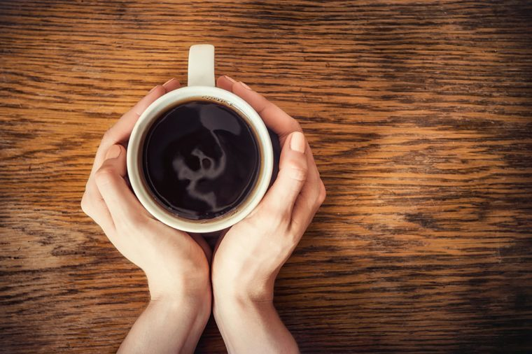 Holding cup of black coffee