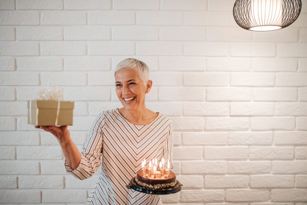 Middle-aged woman celebrating her birthdate with cake