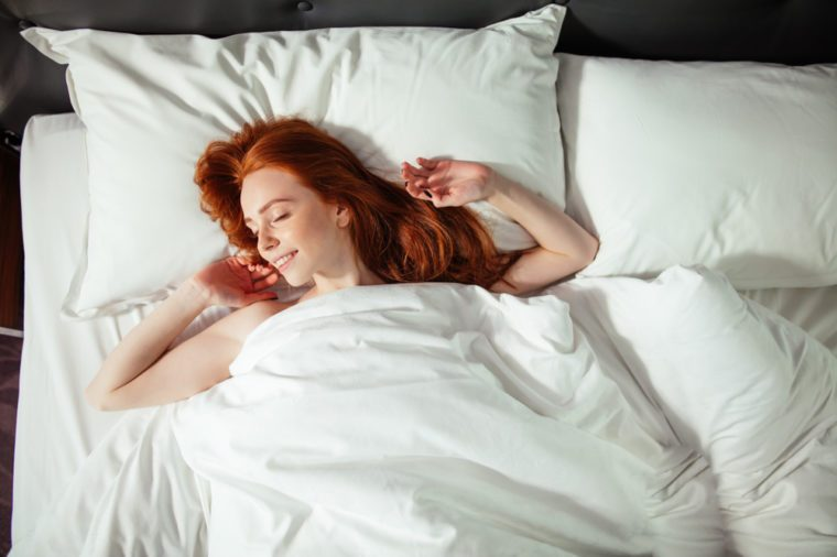 Red-headed woman waking up in bed