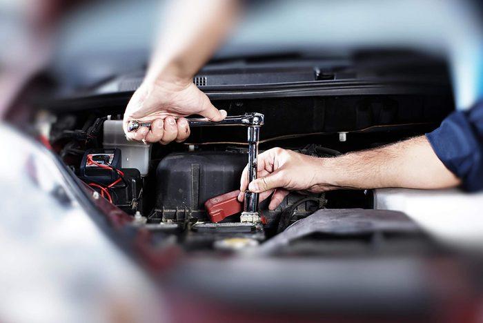 Car mechanic working on engine