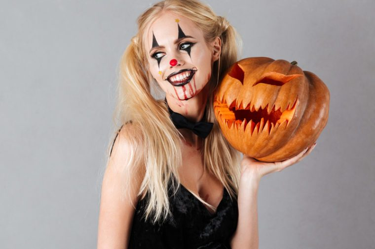 Woman wearing a Halloween costume and carrying a pumpkin