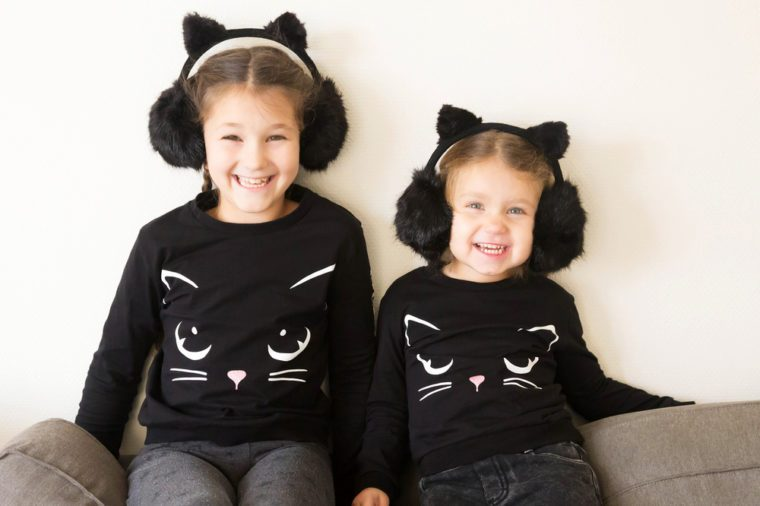 Young sisters wearing cat costumes