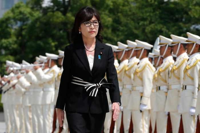 Japan's new Defense Minister Tomomi Inada inspects a honor guard on her first day at the Defense Ministry in Tokyo, . Inada, a woman with revisionist views of World War II history, has been named Japan's defense minister in a Cabinet reshuffle. Japanese Prime Minister Shinzo Abe changed more than half of the 19-member Cabinet on Wednesday in a bid to support his economic, security and other policy goals