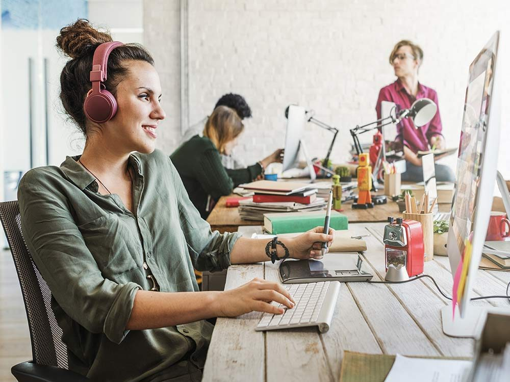 Woman with headphones at desk at work
