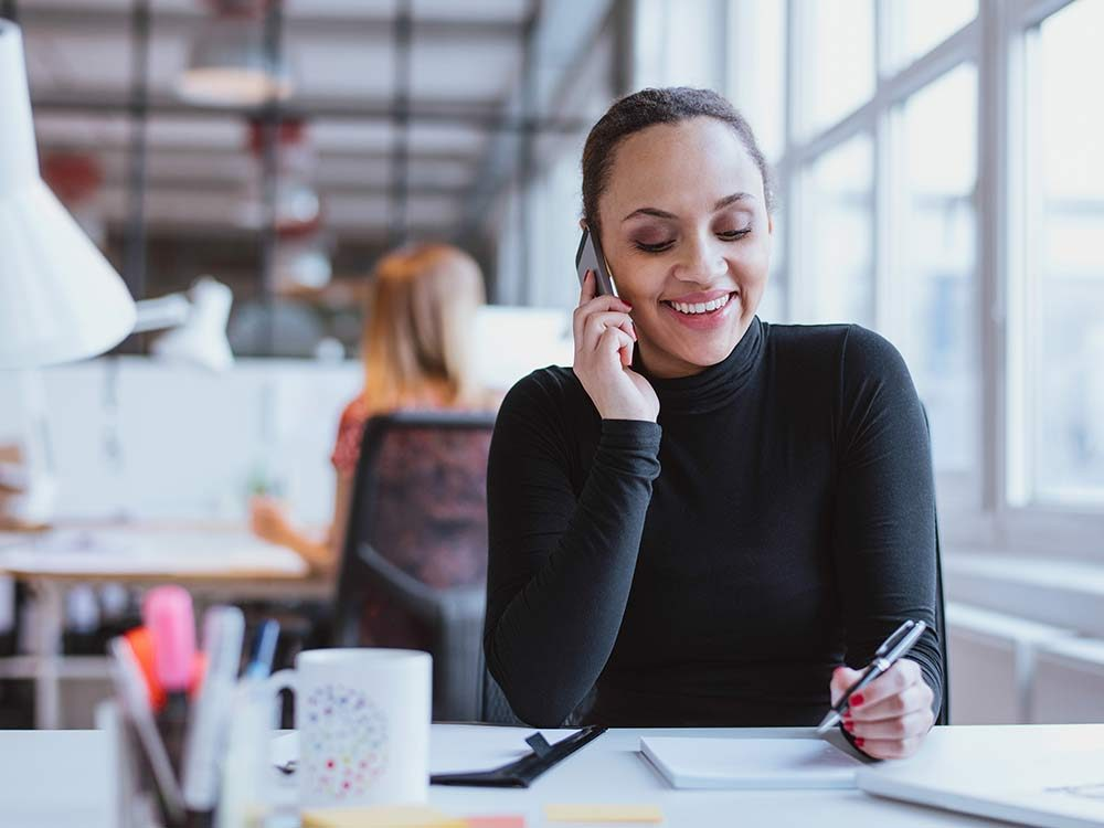 Smiling woman on the phone at the office